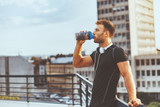 Fototapety Young man resting on the roof of the building after workout and drink water