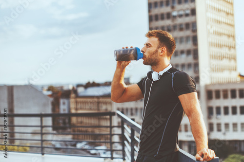 Young man resting on the roof of the building after workout and drink water