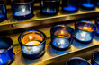 Macro closeup of blue candles with yellow flame in church