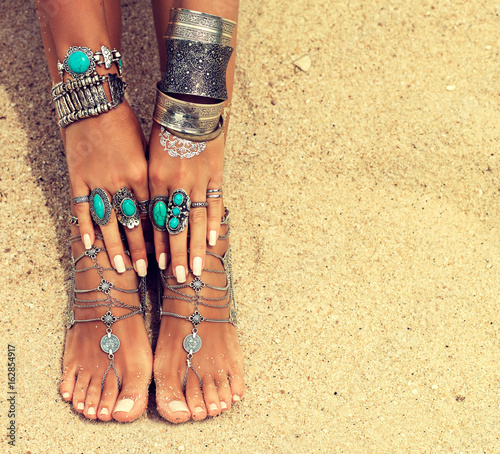 Woman In Relaxation On Tropical Beach with sand , body parts  . Tanned girl leg with silver jewelry,bracelets and rings with turquoise.Boho style feet and hands
