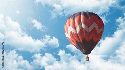 Heißluftballon fliegt vor blauem bewölkten Himmel bei Sonnenuntergang