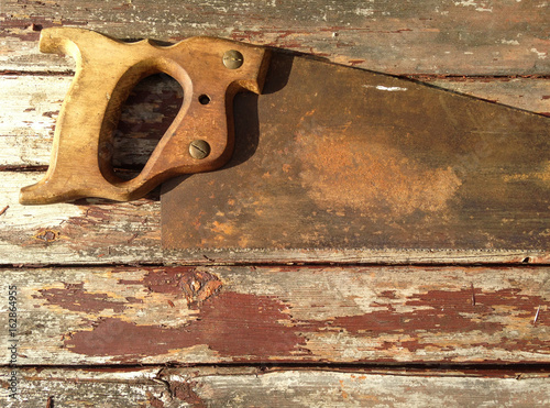 Traditional Wooden Handled Rusty Old Saw on Weathered Wooden Background