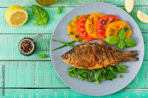 Fried fish carp and fresh vegetable salad on wooden background. Flat lay. Top view - 162867537