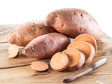 Sweet potatoes on the old wooden table. - 162886515