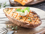 Baked batata on the old wooden table. - 162886544