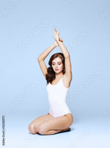 Fit and sporty girl in underwear. Beautiful and healthy woman posing over cyan background. Sport, fitness, diet, weight loss and healthcare concept.