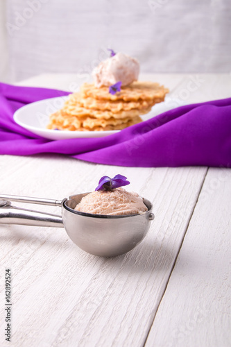 Spoon with ice cream. Belgian waffle on white plate decorated with purple flower.