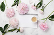 Morning coffee cup for breakfast, empty notebook and pink peony flowers on white stone table top view in flat lay style. Woman working desk.