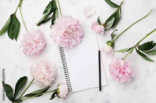 Empty notebook for wedding planning, pencil and pink peony flowers on white stone table top view in flat lay style. Woman working desk. - 162893714