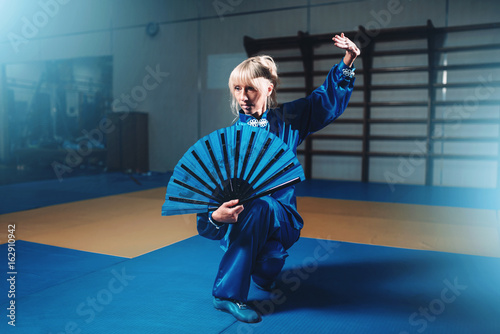 Female wushu master with fan, martial arts
