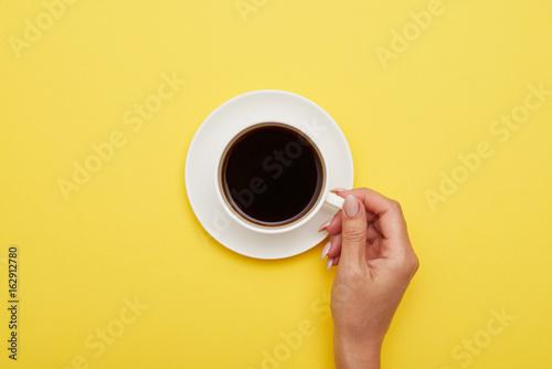 Dziewczyny ręka trzyma filiżankę smakowita kawa espresso, mieszkanie nieatutowy