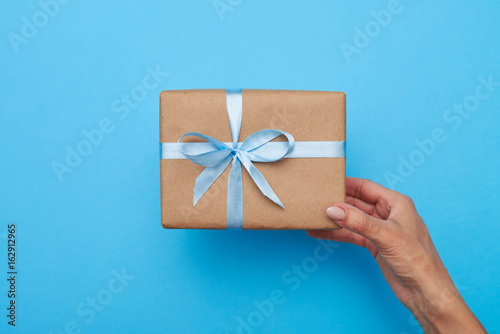 Hands of female holding a gift box over blue background