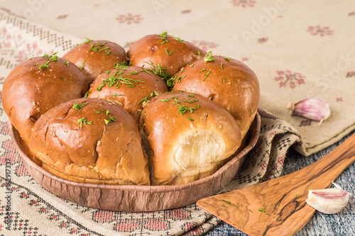 Homemade baking. Freshly baked buns with garlic and fresh greens on a linen tablecloth with an ornament on a gray wooden table.
