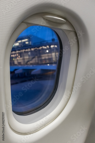 View through the airplane window to the passenger terminal of schiphol airport.