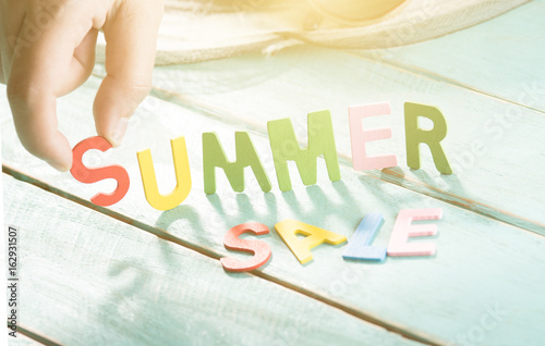 SUMMER SALE word made from colored letters wooden on wood letters with human's finger