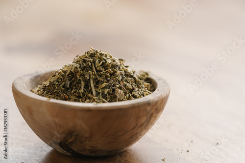 dried provence herb mix in wood bowl for seasoning on table Poster