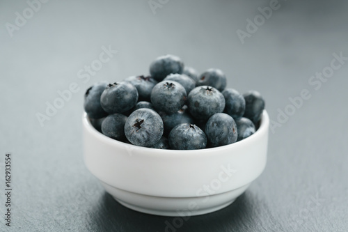 fresh blueberries in white bowl on slate board