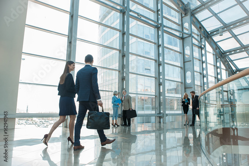 Business people walking in glass building - 162941963