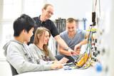 technische Berufsausbildung - Ausbilder mit jugendlichen Azubis im Unterricht an der Berufsschule // trainers with young apprentices © industrieblick