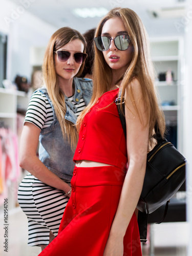 Attractive female models advertising new summer sunglasses collection in fashion store