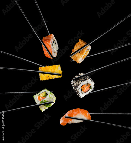 Fototapeta Sushi pieces placed between chopsticks, on black background