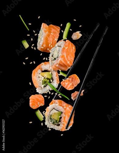 Sushi pieces placed between chopsticks on black background - 162955127