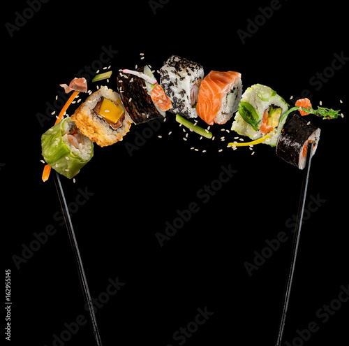 Papiers peints Sushi bar Sushi pieces placed between chopsticks on black background