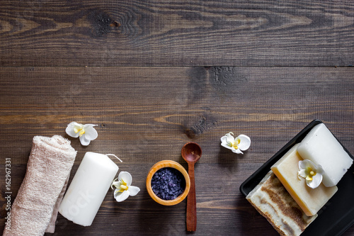 Plexiglas Spa Spa set with salt, flowers and candle on wooden table background top view copyspace