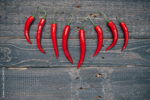 Red hot chili peppers on wooden background. Copy space.