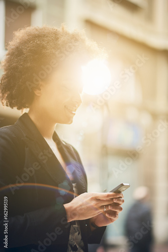 Young businesswoman standing on a street and using smartphone