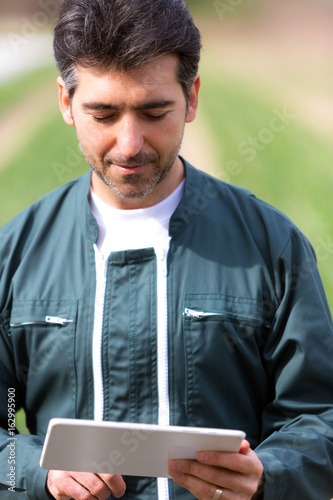Attractive middle aged farmer checking plantation on his field and taking notes on a tablet  - Nature concept