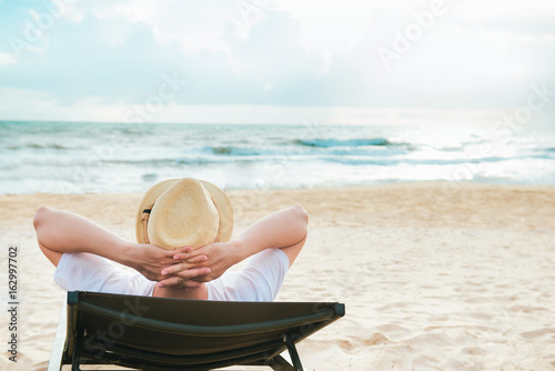 Foto Murales Summer day. Young man lifestyle relaxing with sea view.