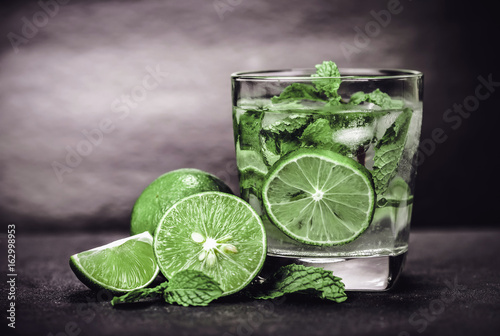 Close up the fresh mojito cocktail with fresh lime and mint leaf on black stone background