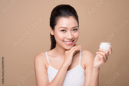 Skincare. Beautiful asian woman show moisturizer or lotion product.