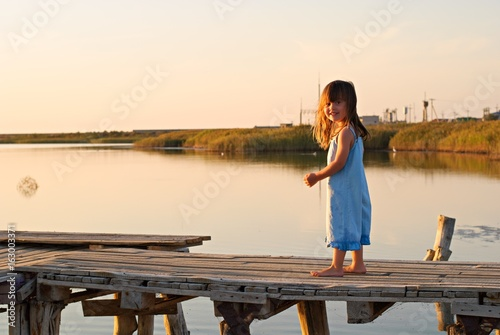 Little beautiful country girl walking along the wooden bridge at