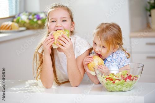 Kinder essen belegte Brötchen zum Frühstück