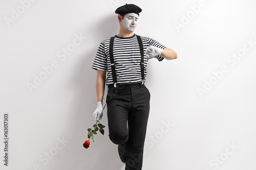 Mime with a red rose looking at an imaginary watch