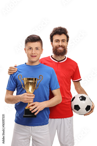 Teenage soccer player holding a golden trophy with his father