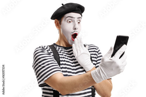 Surprised mime looking at a phone