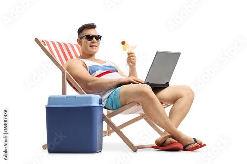 Young man with laptop and cocktail sitting in a deck chair