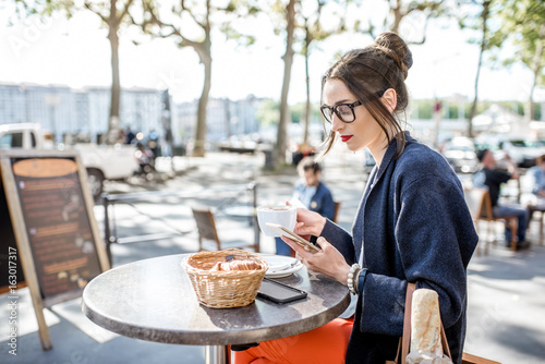 Young woman having a breakfast with coffee and croissant sitting outdoors at the Poster