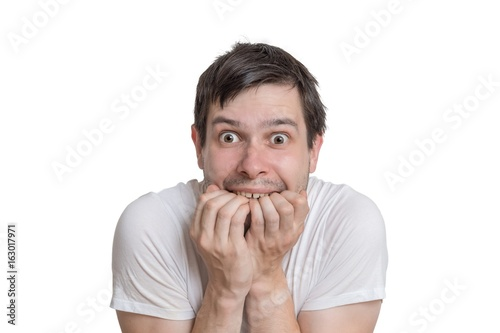 Young scared man isolated on white background.