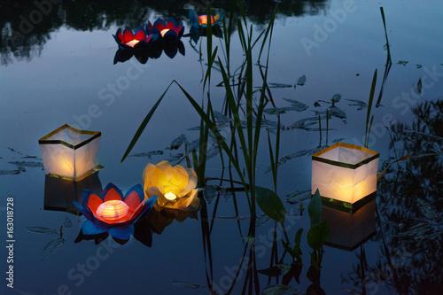 Water burning yellow lanterns on the lake amid tall grass