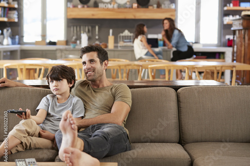 Father And Son Sitting On Sofa In Lounge Watching Television
