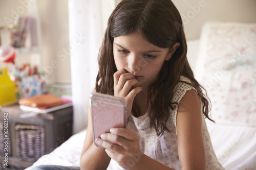 Young Girl In Bedroom Worried By Bullying Text Message