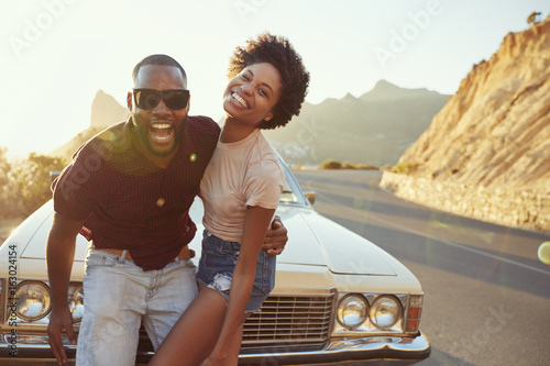 Portrait Of Young Couple Standing Next To Classic Car