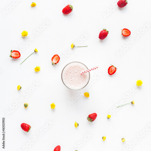 Foto op Aluminium Milkshake Strawberry milkshake, fresh strawberry and yellow flowers on white background. Summer concept. Flat lay, top view