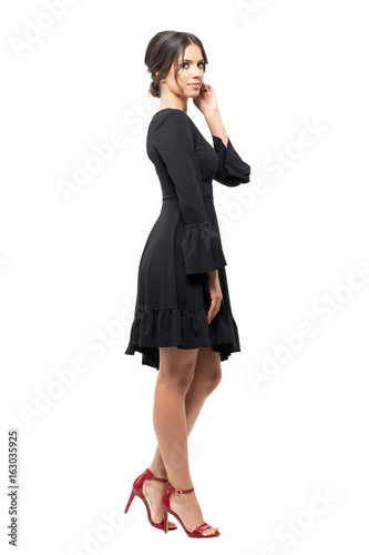 Side view of passionate Hispanic dancer relaxing and touching hair looking at camera.  Full body length portrait isolated on white background.