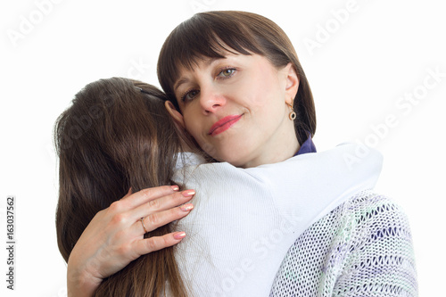 Portrait of a young smiling close-up moms that tightly hugs her daughter
