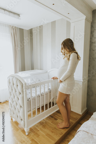 Pregnant woman setting up baby crib